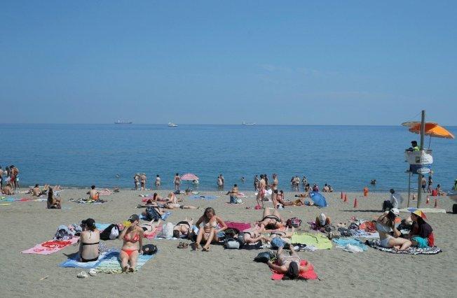 歐洲熱浪來襲,國家近日飆出破紀錄高溫。圖為西班牙南部大城馬拉加民眾湧至沙灘玩水消暑。 (路透)