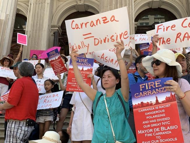 華裔家長朱雅婷(舉標語者)表示,公校多元化改革不應取消SHSAT,而應提高整體教育質量。(記者和釗宇/攝影)