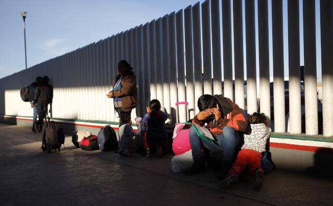 包括處理庇護案官員在內的聯邦政府工會控告川普政府的庇護政策,認為會讓尋求庇護者受到母國迫害。圖為尋求庇護者在墨西哥側的美墨邊牆處等候庇護談話。(美聯社)