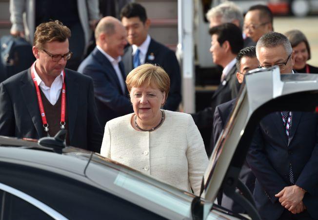 德國總理梅克爾(中)抵達日本,這可能是她最後一次參加G20峰會。(Getty Images)