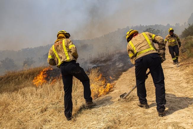 西班牙加泰隆尼亞野火延燒失控,數以百計的消防人員今天奮力滅火。(美聯社)