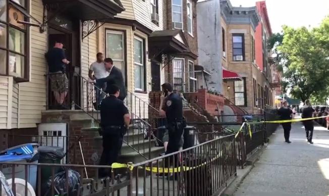 布碌崙(布魯克林)8大道一間住家28日下午發生一起槍殺命案,一名華裔青年疑似臉部中彈身亡。圖為大批警員和警探留守在案發地點展開調查。圖取自影片截圖