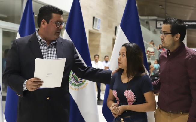 21歲妻子坦妮亞.凡妮莎.阿瓦洛斯的丈夫與二歲不到的女兒,上周在偷渡美墨邊界大河時溺斃。她28日隨兩人遺體返回薩爾瓦多。圖左為薩國外交部長。(美聯社)