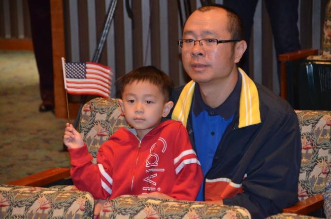 來自廣東的陳先生陪兒子陳冬豪(左)參加入籍儀式。(記者王全秀子/攝影)