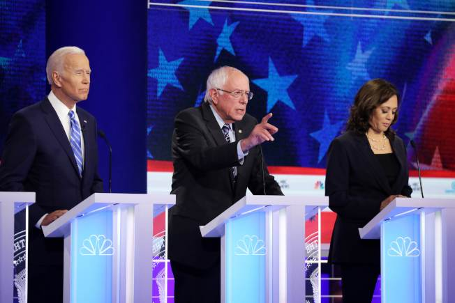 川普對進入第二天的首場民主黨總統初選辯論發表心得,嘲前副總統參選人白登(左)及聯邦參議員桑德斯(中),稱一個精疲力竭,另一個則瘋了。(Getty Images)