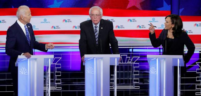 加州聯邦參議員賀錦麗(右)於27日晚的民主黨總統提名初選政見辯論會上,在種族民權問題上,狠狠修理民調領跑者前副總統白登(左),讓白登重重摔跤,領先地位不保。中為聯邦參議員桑德斯。(路透)