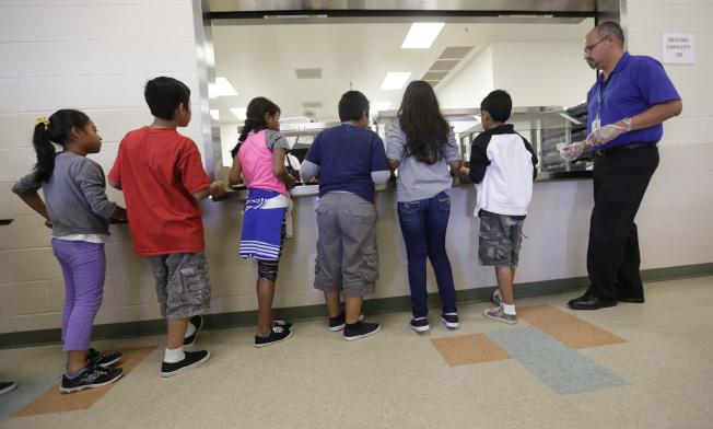 公民及移民服務局實施的新政策取消「沒有大人陪伴的未成年人」的地位,讓18歲以下尋求庇護者更易遭驅逐出境。圖為遭拘留的移民兒童在德州一所拘留中心排隊領取食物。(美聯社)