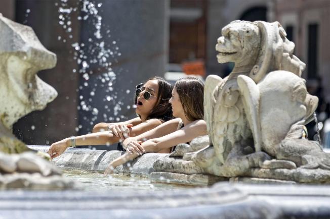 羅馬炎熱,遊客們在古蹟廣場利用噴泉「冷」靜一下。(歐新社)