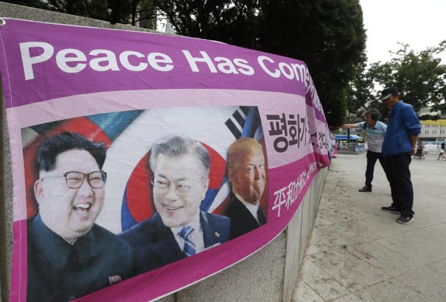 美國總統川普29日赴南韓訪問兩天,反對川普到訪的民眾在首爾美國大使館外掛上橫幅,上有北韓領導人金正恩(左至右)、南韓總統文在寅及川普肖像。(美聯社)