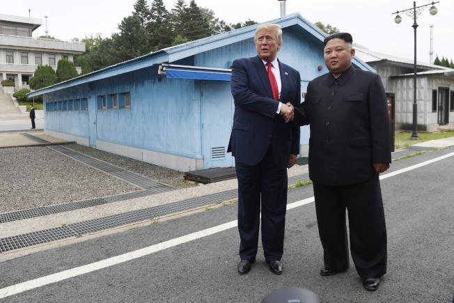 川普(左)與金正恩30日在DMZ歷史性握手。(美聯社)