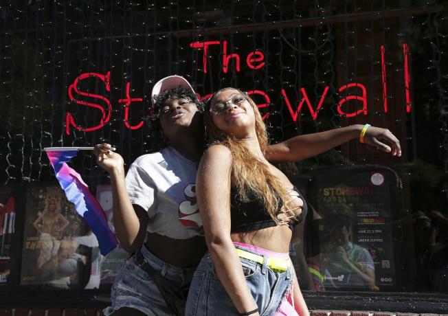 民眾在50年前發生同志史知名「石牆事件」的酒吧外留下合影。美聯社