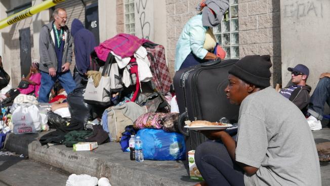 洛市遊民領取食物後在路邊用餐。(記者李雪/攝影)