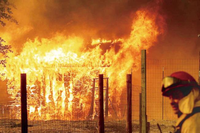 2018年7月牧場山火(Ranch Fire),一名消防隊員正在監控燃燒的建築物,確保火苗不會蔓延。(美聯社)