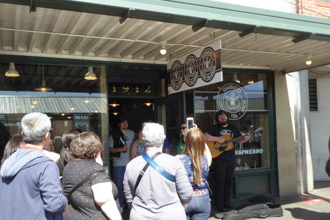 星巴克咖啡成立於1921年的首店,門口排著長隊門外有藝人彈奏吉他。