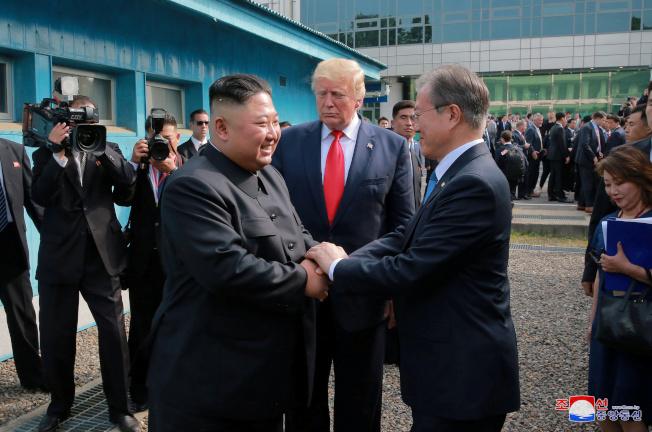 川普總統(左)和北韓領導人金正恩(中)6月30日結束在板門店停戰村談話結束後,離開自由之屋,南韓總統文在寅在外迎接。這是首次南北韓領導人與美國總統合影。(路透)