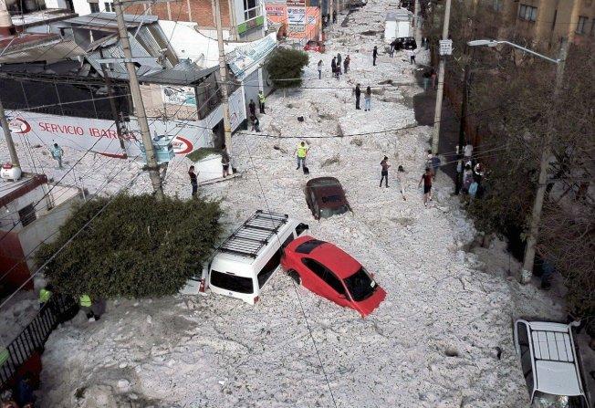 墨西哥第二大城、哈利斯科州首府瓜達拉哈拉(Guadalajara)6月30日晚間發生異常氣候,盛夏冰雹暴風雨突降,把整個城市埋在最高2公尺的冰雪堆中,城內6處郊區受災嚴重,反常的氣候嚇壞不少當地居民,放眼望去白靄靄一片,畫面格外驚人。圖╱GettyImages