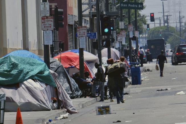 雖然就業率高,經濟向前發展,但詭造成社會貧富懸殊現象嚴重,各大城市都有遊民大軍,住宿街頭。圖為洛杉磯市內街頭遊民。(美聯社)