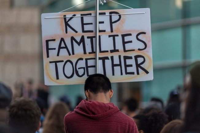 川普政府計畫徵用國內軍事基地改為拘留中心,來關押被捕無證移民與家庭。但引發民眾抗議。圖為在加州洛杉磯附近的日裔美人博物館前抗議民眾,手持 「讓家庭團聚」標語。(Getty Images)