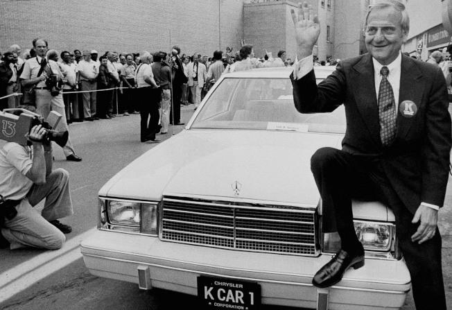 「汽車巨人」艾科卡1980年坐在克萊斯勒K Car Number One引擎蓋上的英姿。(美聯社)