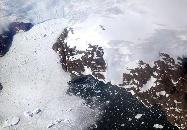 由於氣候變化,格陵蘭今年融冰比往年提早。圖為2017年格陵蘭一條冰川崩解融化。(美聯社)