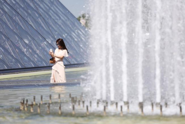 法國在6月份出現45℃高溫,圖為遊客在巴黎羅浮宮噴泉旁自拍。(新華社)