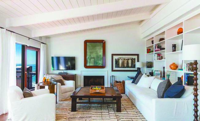 主要起居室中設有高高的木橫梁天花板和一個壁爐。(Realtor)