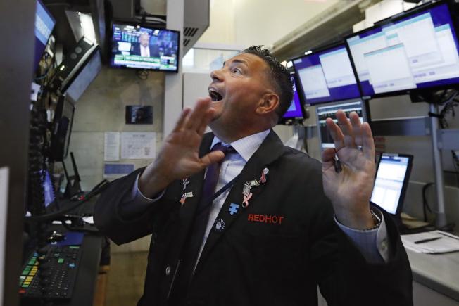 押注聯準會必定降息,美國三大股指在國慶日前夕同創新高。圖為紐約證交所交易員望著大盤指數。(美聯社)
