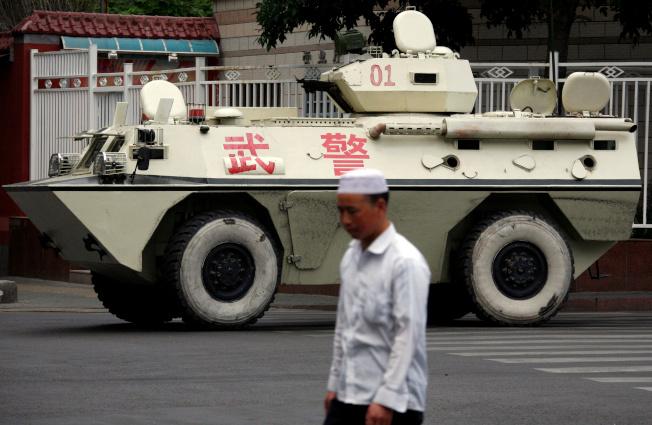 新疆街頭一名民眾路過武警裝甲車。(路透資料照片)