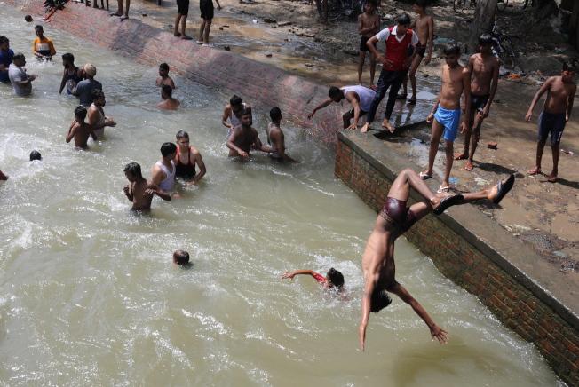 印度熱浪來襲,少年2日在西北部城市阿姆利則的運河中玩水消暑。(歐新社)