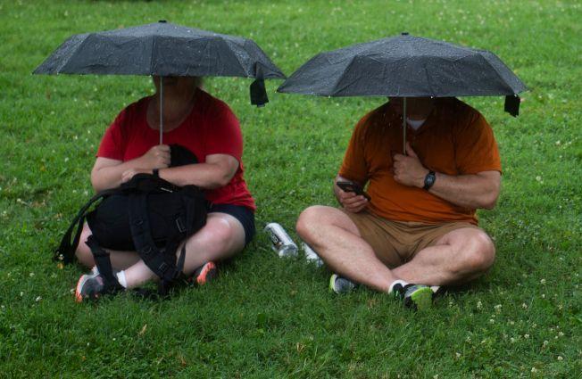 一對夫妻在「向美國致敬」活動中,各撐一把雨傘坐在草地上。(Getty Images)