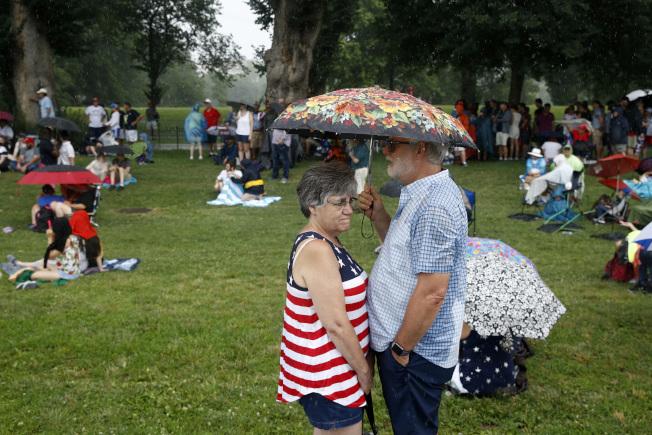 一對夫妻在「向美國致敬」活動中,共享一把雨傘。(美聯社)