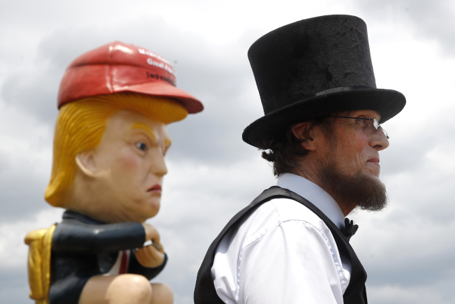 來自紐約州的Everett Loud,打扮成林肯總統的模樣,與坐在馬桶上、手持手機的「川普 寶寶」相映成趣。 (美聯社)