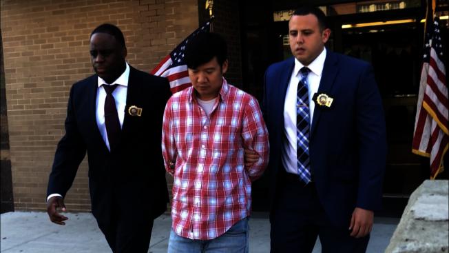 身穿紅白格子襯衫的兇嫌(中)在兩名警探的護送下離開警局。(記者顏潔恩/攝影)