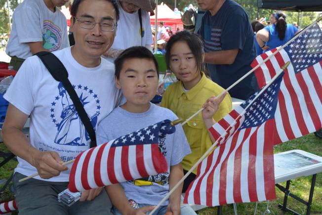 華人謝先生(左)與一雙兒女第二次參加岡國慶大遊行。(記者啟鉻/攝影)