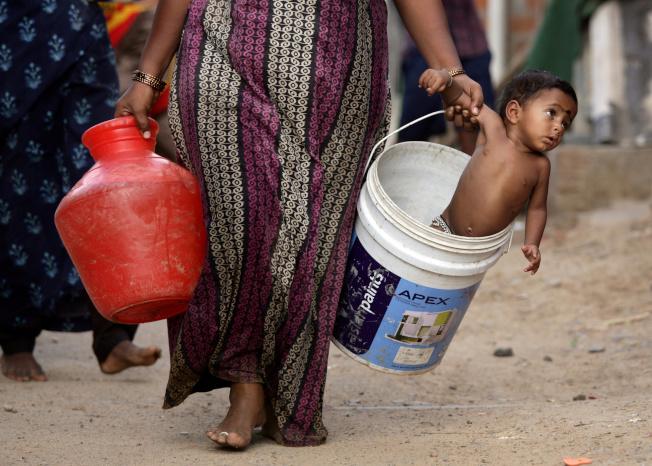 一名印度婦女從政府提供的水車取水後,將她的兒子放在桶裡。(路透)