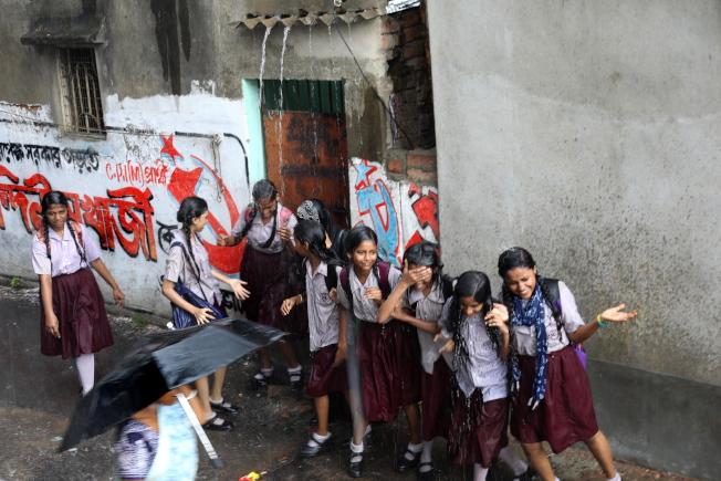 陣雨過後,加爾各答一群女學生一日爭相淋著屋頂流下的雨水。(歐新社)