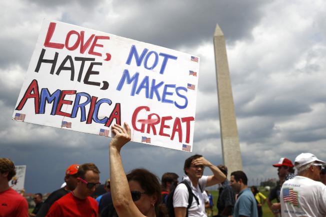 華府「向美國致敬」活動 ,一位女性手持「是愛,不是恨,讓美國更偉大」的牌子。(美聯社)
