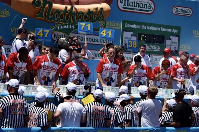 比賽計時一開始,台上選手立即快速地吃起熱狗。(記者顏潔恩/攝影)