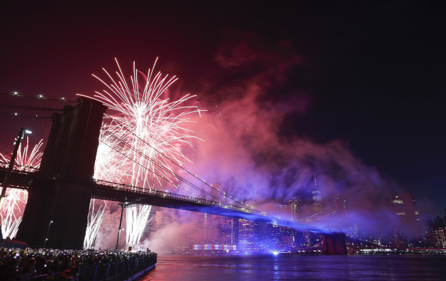 梅西國慶煙火秀,4日晚在東河上演,絢爛焰火映照著布碌崙大橋。(美聯社)