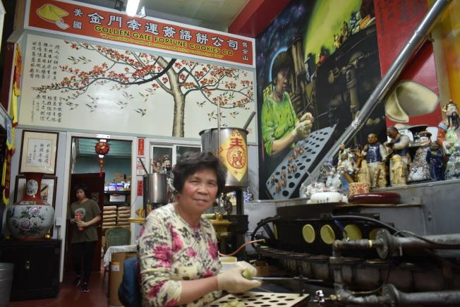 陳展明母親數十年如一日地製作簽語餅,身後是她年輕時同樣製作簽語餅的艱難創業畫像。(記者黃少華/攝影)