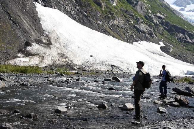 阿拉斯加州受熱浪侵襲,當地的拜倫冰川加速融解,圖為兩名健行者走近冰川下的小溪。(Getty Images)