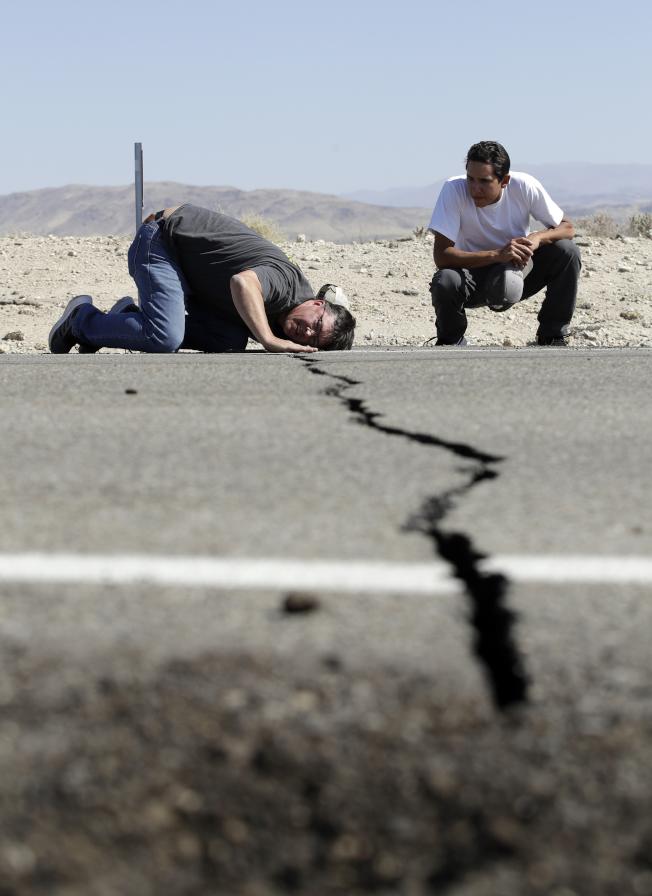 南加州連番出現強震,高速公路被震出裂縫,圖為兩名男子在里奇克萊斯特附近檢查公路斷裂的程度。(美聯社)