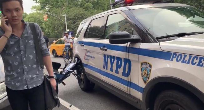 該華男騎共享單車被警方截停時,單車捲入警車車輪。(目擊者視頻截圖)
