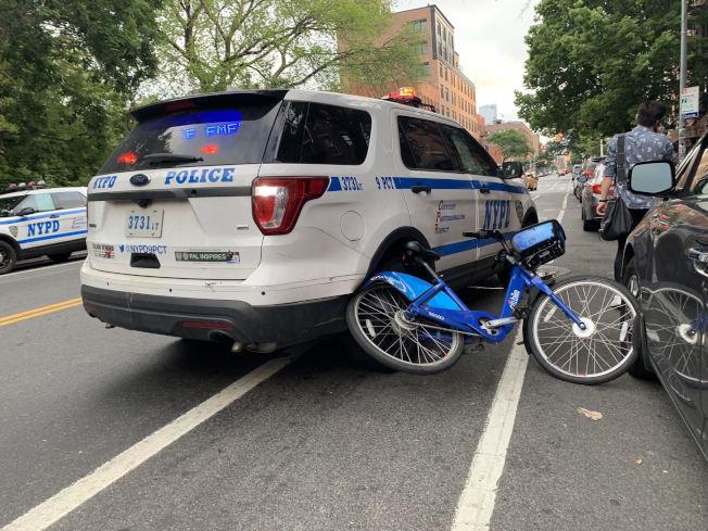 一名華男騎共享單車被警方截停時,單車捲入警車車輪。(目擊者視頻截圖)