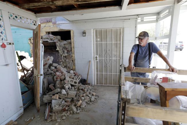 南加州地震過後,工作人員開始評估特羅納的建築物、道路、水管、瓦斯管和其他公用事業的受損程度。圖為當地一戶人家的房屋損毀,屋主無奈地望著倒塌的煙囪。(美聯社)