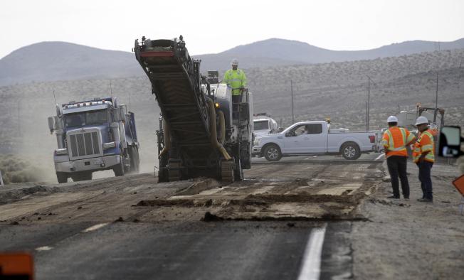 工作人員7日在特羅納附近搶修178公路的一段路面。(美聯社)