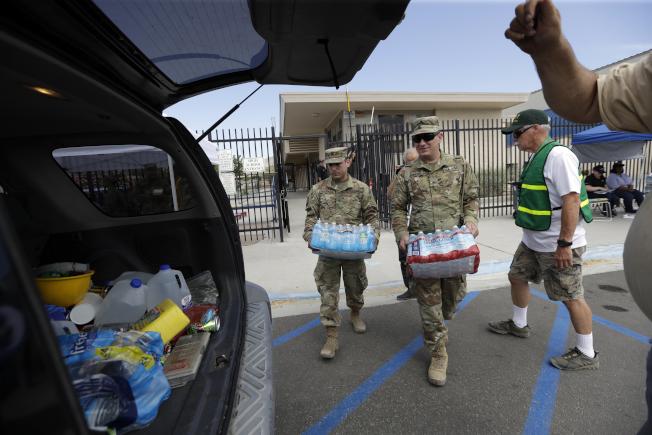 國民兵成員7日把瓶裝水運往南加州地震災區。(美聯社)