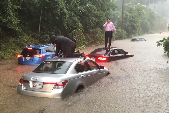 華府8日早上一場大雨造成淹水。圖為駕駛者爬到車頂上求救。美聯社