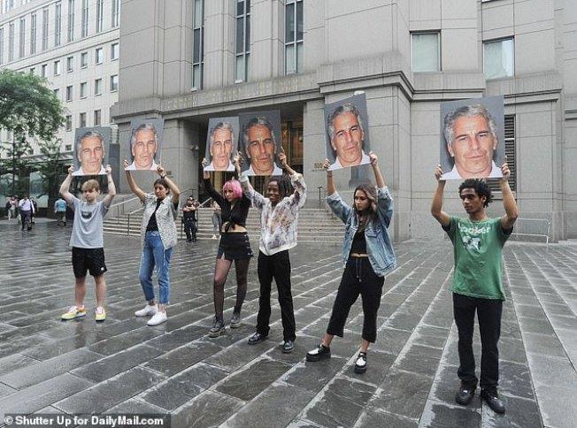 在法院外有民眾舉著被告艾普斯坦的照片,表示一定要之以法。(Getty Images)