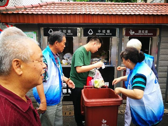 曲陽街道志願者正在幫居民垃圾分類。(取材自澎湃新聞)